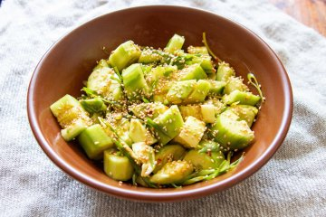 A big bowl of smashed cucumber salad with toasted sesame seeds