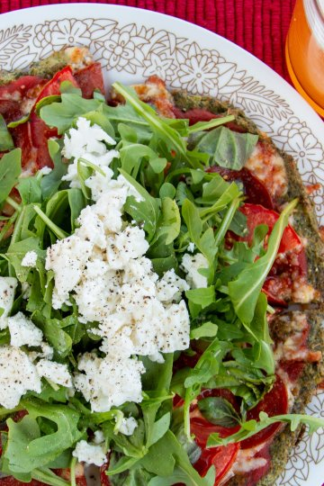 Broccoli crust pizza topped with more greens and crumbly cheese