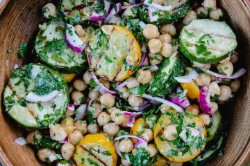 A delicious looking bowl of grilled zucchini and chickpea salad with red onions