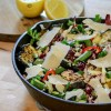 A mixed vegetable skillet salad in a cast iron pan with some lemon wedges on the side