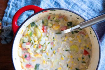 A big pot of hearty corn chowder with a ladle