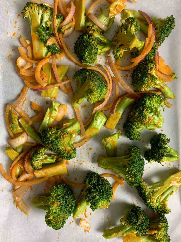 spicy broccoli ready to roast on a tray