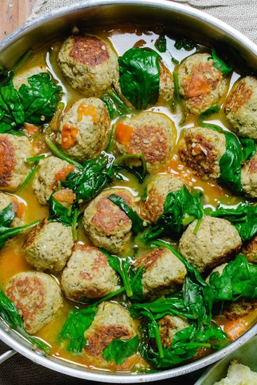 a pan of turkey meatballs in broth with wilted spinach.