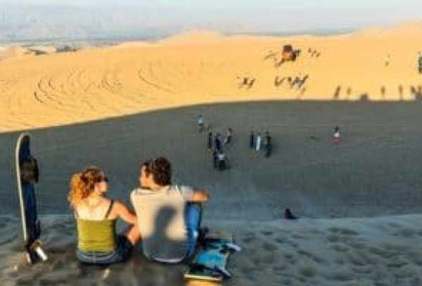Sanboarders couple admiring the view off the top of sand dune