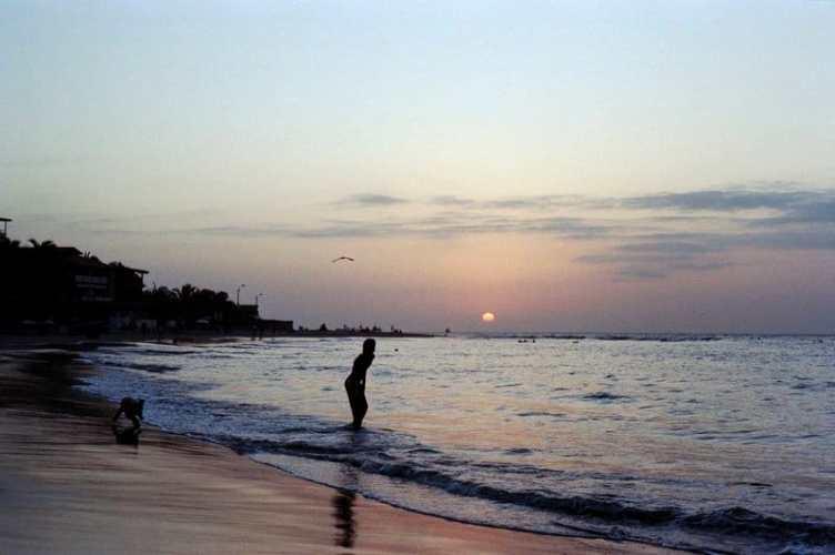 Beach mancora at night sunset man paddling