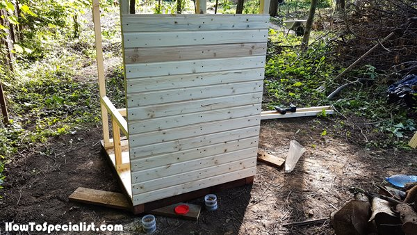 Attaching-the-slats-to-the-back-of-the-outhouse