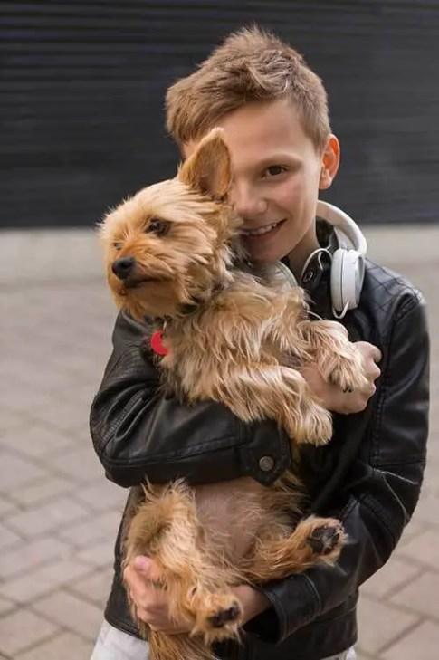 a cute boy holding his dog