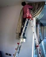 Hängen von handgesäumten, bestickten Leinenvorhängen in einem Privathaus
