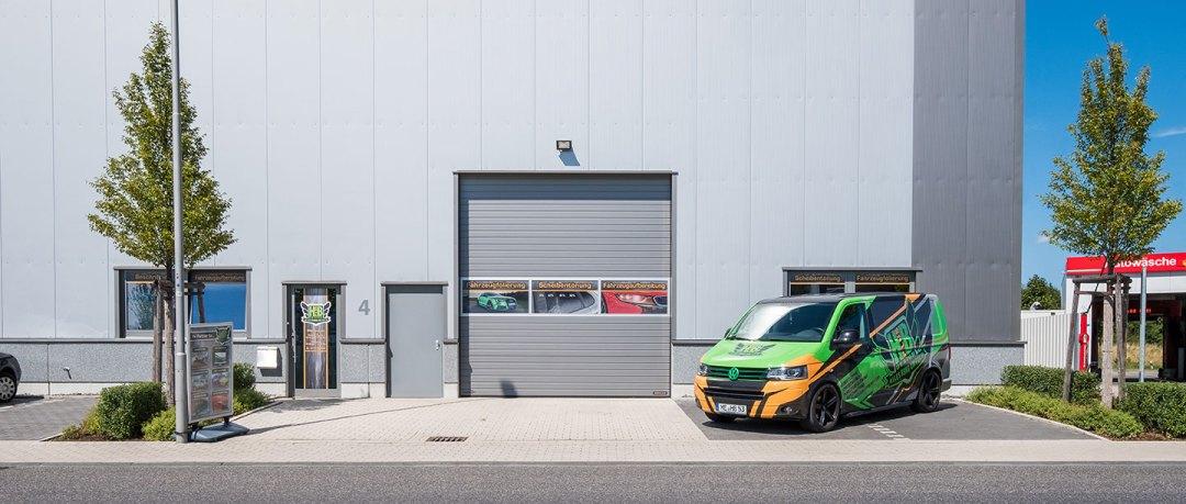 VW Bus mit grüner Folienbeklebung, getönten Seitenscheiben und schwarzem Logo von HplusB Design