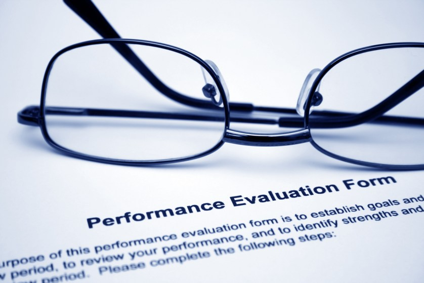 Performance Management - Close up of glasses on performance evaluation form