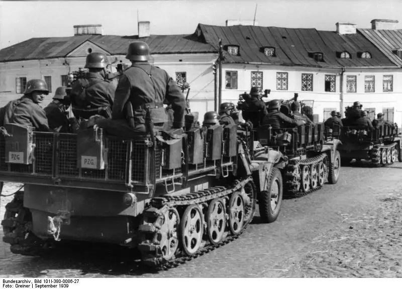 Kolumna trzech pojazdów półgąsienicowych przewożących żołnierzy. W tle białe piętrowe budynki mieszkalne.