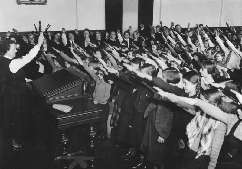 Dziewczynki i chłopcy w wieku ok. 10 i 11 lat stoją przed nauczycielką na katedrze. Wszyscy wznoszą prawe ręce w geście Heil Hitler.