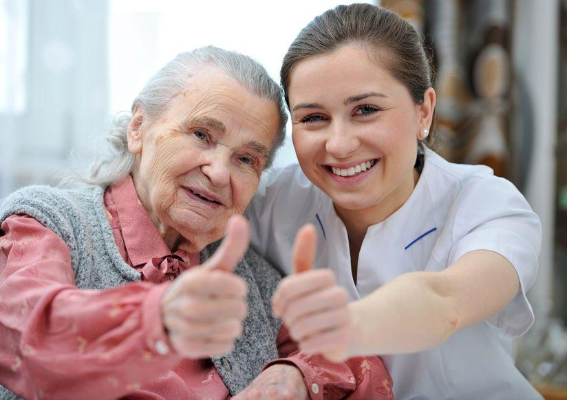 Frau mit Pflegerin mit jeweils Daumen hoch