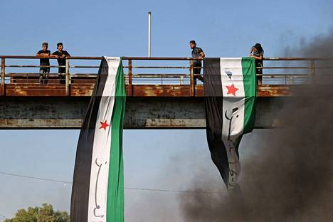 Syrians hang an opposition flag over a highway in the city of Ariha in the rebel-dominated Idlib province on July 25.