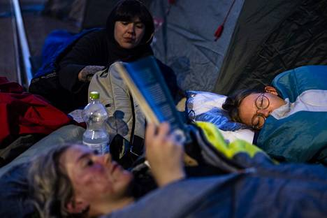 Protesters in the August Rebellion spent the night on Mannerheimintie between Thursday and Friday.  Silja Laitinen read a book at the end of the demonstration on the side of the Parliament House, Vilja Westerberg (right) had already gone to sleep.  Behind Rauna Lilja.