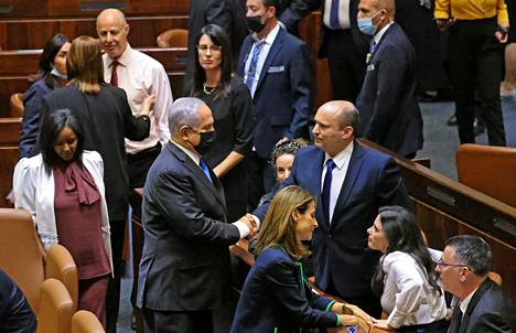 The resigned Prime Minister Benjamin Netanyahu and the new Prime Minister Naftali Bennett shook hands in the Israeli parliament on Sunday.