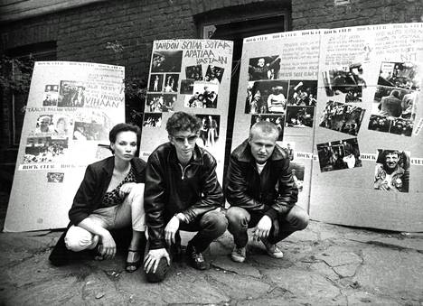 """Maukka Perusjätkä (right), Ralf Örn and Maija Byckling in the yard of Kallio's Kill City in 1979 behind him an exhibition emphasizing the importance of the house as a functioning youth base.  The petitions did not help, the whole block of wooden houses was demolished.  The final stages of Kill City were filmed in the most popular Finnish film of 1980, Here Comes the Life !, where Maukka Perusjätkä sang two songs and said with a sigh """"Huame will be the catapillers""""."""