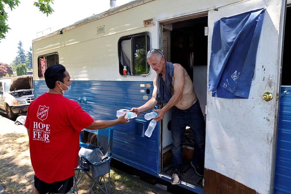 A Salvation Army employee handed water bottles to Eddy Norby, who lives in a caravan in Seattle.