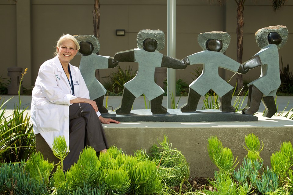 Astrid Heger, MD, empathy program lead, photographed outside at the Keck School campus, sitting by a statue of children dancing. She is wearing doctoral clothing, smiling and looking into the camera.
