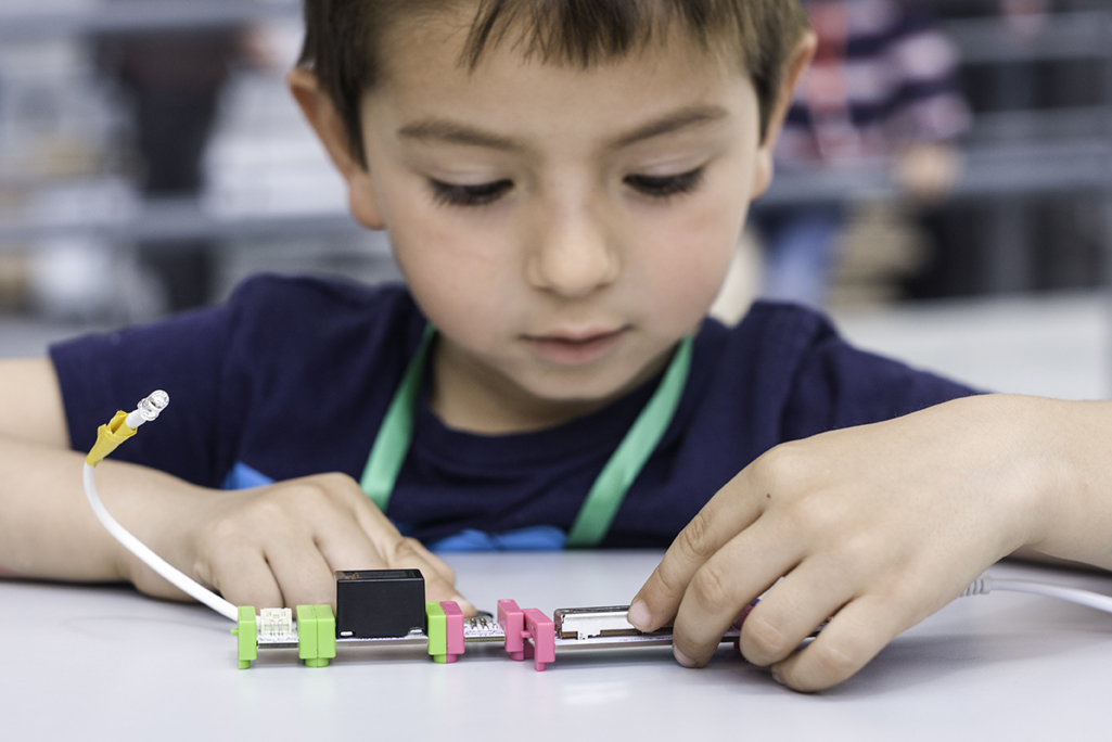 Stock image of little boy experimenting with circuits in science class