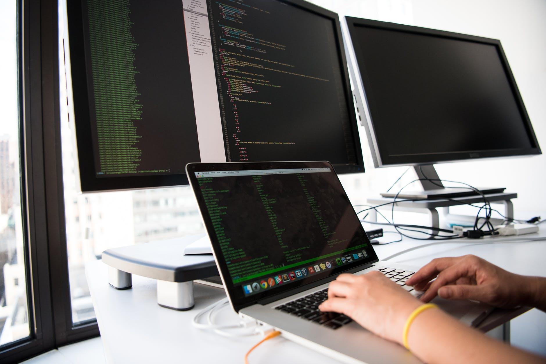 pessoa configurando computadores para garantir a cibersegurança