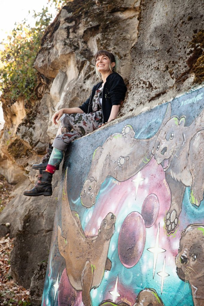 Kara Harrison poses with her newly painted mural, Otters In Outerspace