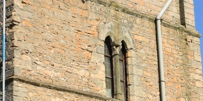 Close up of south face of tower, showing eroded stonework and mortar