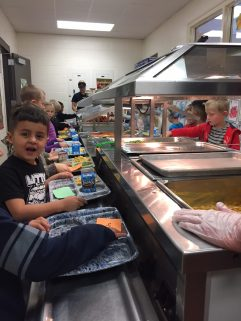 Elementary students passing through the food service line.