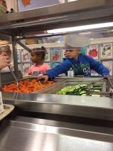 Two elementary students reaching for carrots in the school lunch line.