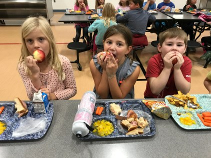 Three elementary students seated in the cafeteria biting into apples.