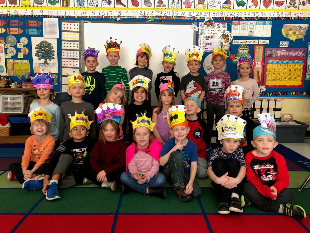 A group of kindergarten students pose with their 100 days hats.
