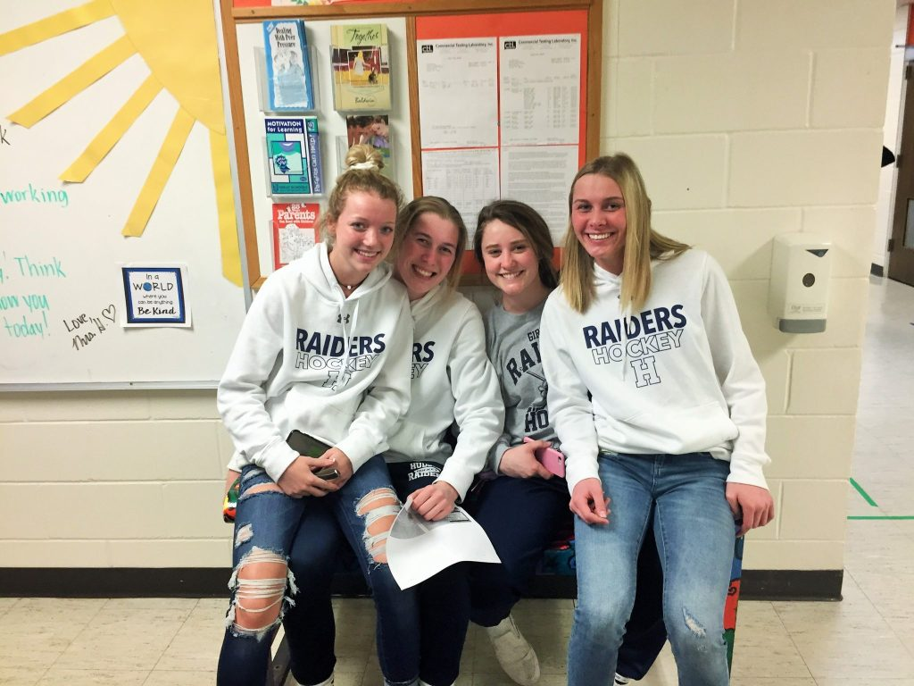 Four members of Hudson High School girls' hockey at Houlton Elementary.
