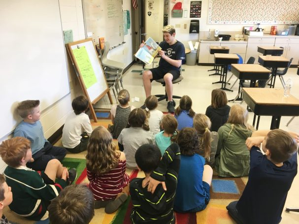 High school student sitting in a chair reading to elementary students sitting on a classroom floor.