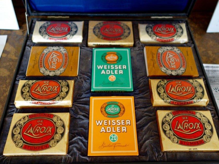"""Detailansicht - Der schmale Holzkoffer ist innen mit Samt ausgeschlagen und mit elf Zigarren-Schaupackungen der Firma de la Crox Cigarren aus Friedrichstal versehen. Innen ist der Deckel mit blauer Kunstseide bespannt und zeigt eine ovale Kartusche mit der Aufschrift """"ORIGINAL DE LACROIX sprich: lakroa CIGARREN"""", darunter """"de la Croix Cigarrenfabrik Friedrichstal Baden gegr. 1885"""". Mit Schaukoffern wie diesem priesen Vertreter der im badischen Friedrichstal ans‰ssigen Zigarrenfabrik De la Croix ihre Ware bei potentiellen K‰ufern im Einzelhandel und Gastgewerbe an. F¸r das badische Dorf Friedrichstal dokumentiert der Musterkoffer die Zeit der Tabakindustrie im 19. Jahrhundert, in der Baden neben Preuflen das grˆflte Tabakanbaugebiet Deutschlands darstellte. Die in der Markgrafschaft Baden-Durlach und dem Bistum Speyer aufgenommenen Hugenotten hatten hatten Tabaksamen und Kenntnisse ¸ber den Tabakanbau aus Frankreich und ihrem zeitweiligen Aufenthalt in der Pfalz mitgebracht und schufen damit die Voraussetzung f¸r die weitere Verbreitung des Anbaus in Deutschland. Eine von ihnen gez¸chtete Tabaksorte wurde nach der neuen Heimat """"Friedrichstaler"""" genannt."""