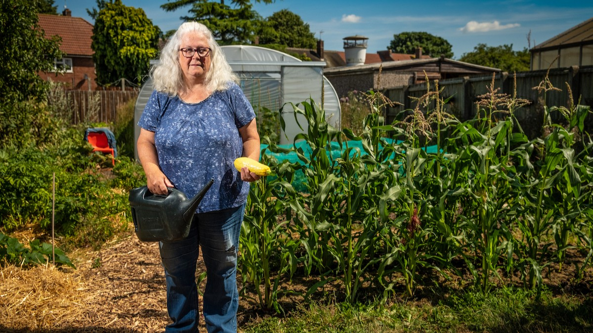 Photo of a community grower holding a watering can in front of a vegetable garden