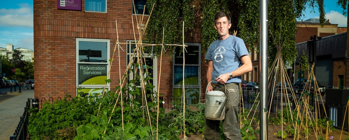 Photo of a man standing in front of a vegetable garden next to the Wilson centre