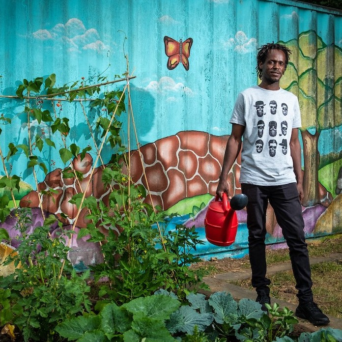 A young person holding a watering can stand sin front of a garden with a vivid and colourful mural wall.
