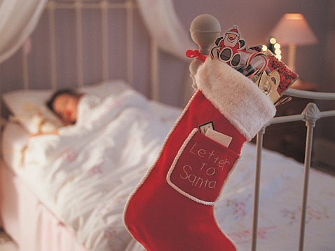 Christmas Stocking Hanging on a Bed Knob and a Child Sleeping in Bed in the Background