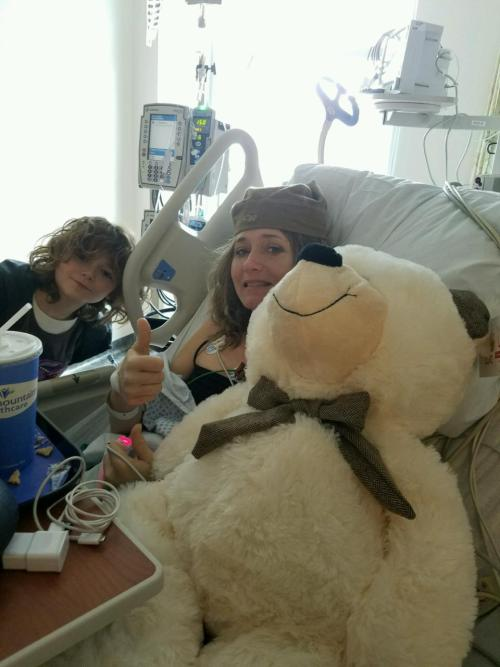 Karen with Isaac in the hospital ER the afternoon after she was rescued. The hat she is wearing belonged to the sheriff who rescued her, the polar bear a gift from Isaac.