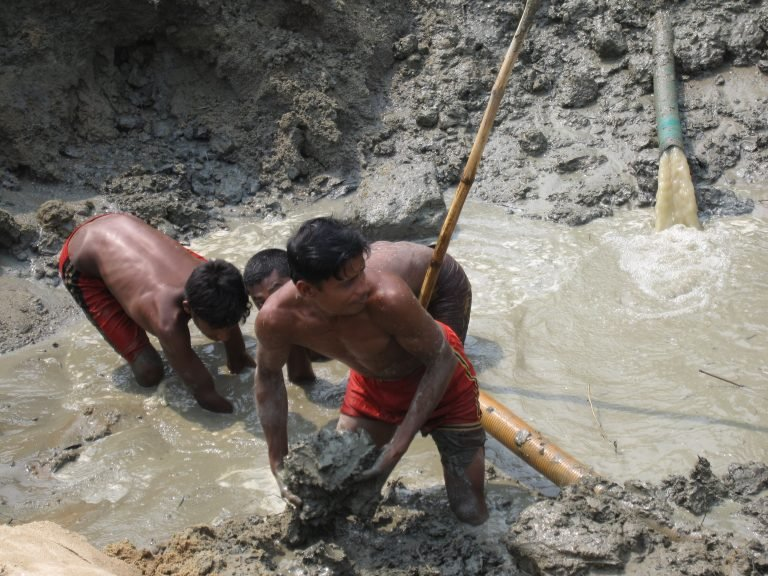 In Bangladesh, a crew excavates a riverbed for a new bridge. Outdoor labor is a way of life in many regions subject to the worst heat and humidity..