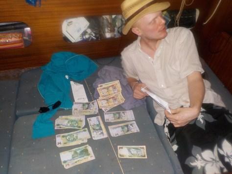 photo de Roux dans le bateau avec plein de billets jamaïcains posé sur le coussin