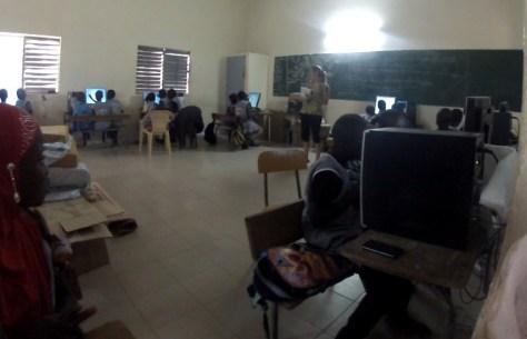 photo de la salle informatique avec élodie et les élèves assis derrière les machines