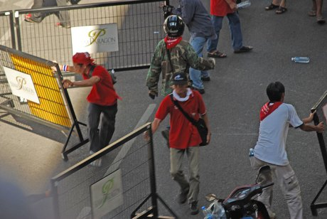 """""""Red shirt"""" anti-government protesters move barricades without resistance outside a Bangkok mall."""