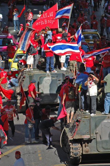 """Anti-government """"red shirt"""" protesters climb on top of two tanks outside a busy Bangkok mall."""