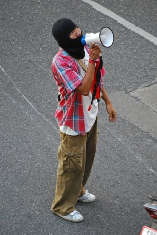 "A ""red shirt"" protester wearing a mask uses a megaphone to help coordinate outside Bankok's Siam Pavilion mall."