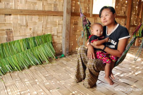 A Nu Mya holds her youngest son, age 2, inside their Myanmar home.