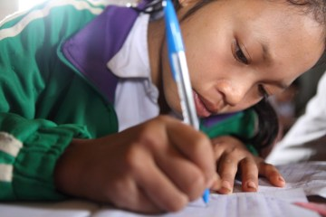 A young girl works hard in her classroom in Laos.
