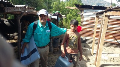 World Concern Program Manager Ye Win Tun helps 14-year-old Lesout carry a tarp and water jug home from the distribution.