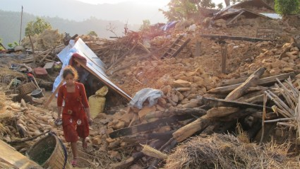 A young girl walks near her tent amidst the rubble in Khalte, Nepal.