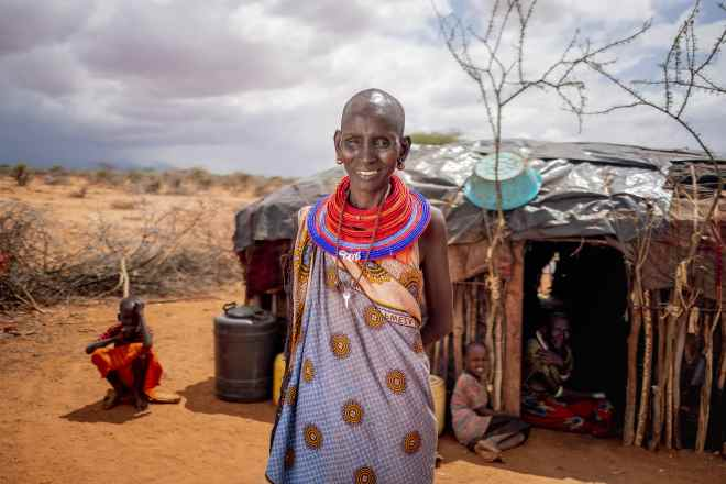 a woman smiles outside her hut in Kenya